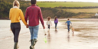A family and a pet dog walking along a beach